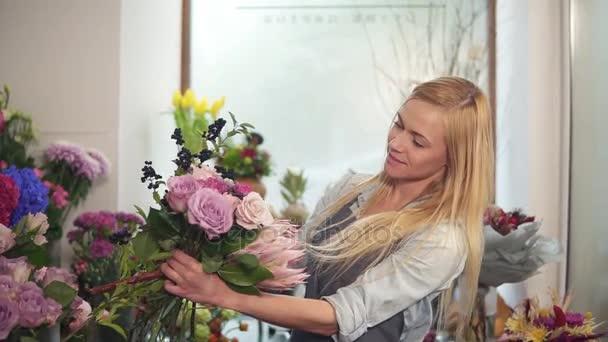 Young female florist arranging modern bouquet, young handsome florists work at flowers shop making bouquet. Slowmotion shot