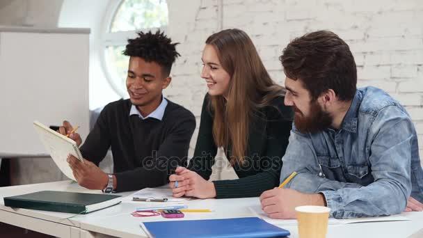 Mnohonárodnostní skupiny lidí pracují společně. Mladí Afričan něco vysvětlovat jeho kolegové. Happy různorodá skupina Studenti nebo mladí obchodní tým pracuje na projektu. Slowmotion shot