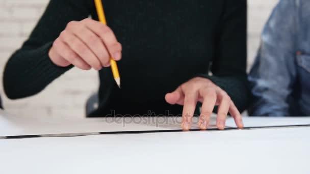 Mnohonárodnostní skupina lidí pracujících společně Rozměrový plán pomocí tužky a pravítka. Happy různorodá skupina Studenti nebo mladí obchodní tým pracující na projektu. Slowmotion shot