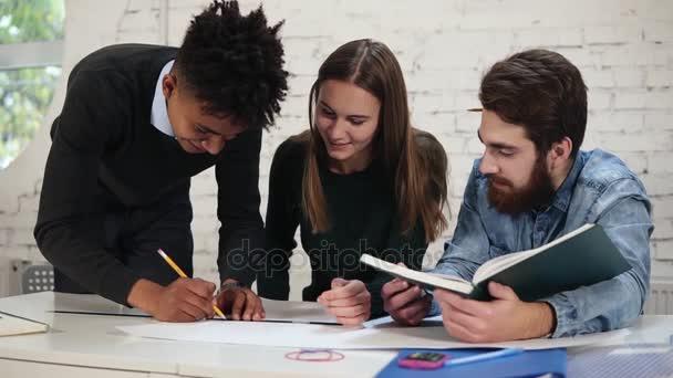 Různorodá skupina lidí pracujících společně Rozměrový plán, pracující na projektu. S úsměvem africké úřednice kresba projekt postavení v tabulce, zatímco jeho colleques mu pomáhají