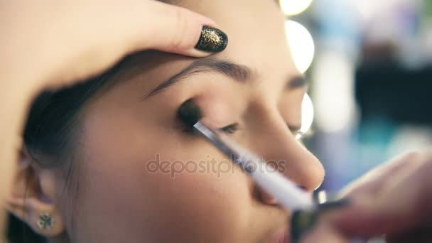 Detailní pohled na profesionální make-up artist rukou pomocí make-upu štětec použít oční stíny. Pro vizážistiku klade světle hnědé stíny na oční víčka modelu. Slowmotion shot