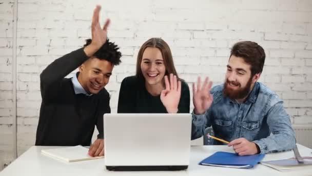 Eine fröhliche und attraktive gemischte Gruppe junger Berufstätiger trifft sich zu einem Geschäftstreffen oder einer Diskussion über das Internet. Sie lächeln und winken, während sie ihren Kollegen begrüßen. Langsame Entwicklung
