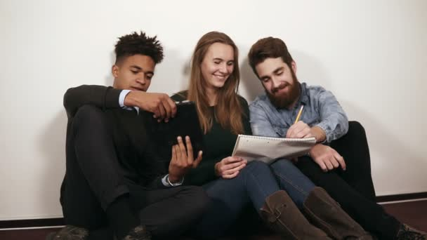 Happy různorodá skupina Studenti nebo mladí obchodní tým pracuje na projektu. Sedí na podlaze a práci s notebooky a digitální tablet. Slowmotion shot