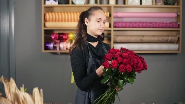 perfekte Bouquet von roten Rosen von professionellen Floristen: junge attraktive Floristin arrangiert Bouquet von schönen roten Rosen im Blumenladen. Zeitlupenschuss