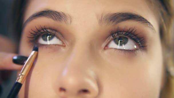 Nahaufnahme von professionellen Make-up-Künstler Hände mit Make-up Pinsel Lidschatten aufzutragen. Zeitlupenschuss