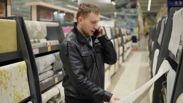 Giovane uomo sta chiamando qualcuno di essere consultato mentre la scelta di sfondi in supermercato. Guardando la carta da parati, toccarlo è pensare che uno è migliore