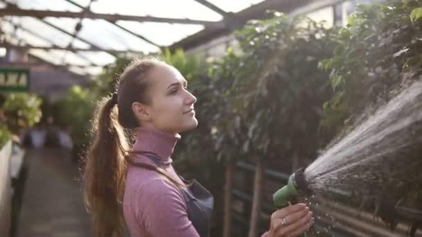Detailní pohled na mladou atraktivní ženské zahradník rovnoměrné zavlažování rostlin s zahradní hadice ve skleníku