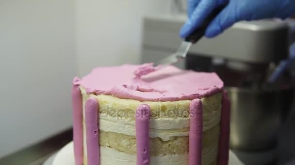 Konditor Anwendung Puprle Schlagsahne oben auf Keks-Kuchen mit Blätterteig Spachtel Gleichsetzung. Erstellen leckeren Kuchen. Essen-Kunst.
