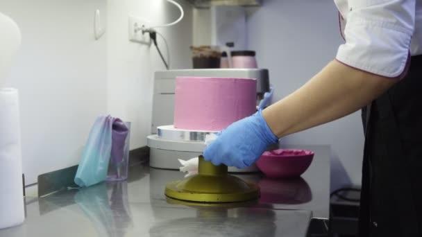 Eine lila Torte auf spezielles Tablett Spinnen beim Abschluss dekorieren es. Nehmen extra Schlagsahne Sahne aus Boden. Konditor Essen-Kunst. Köstliches Dessert zu machen.