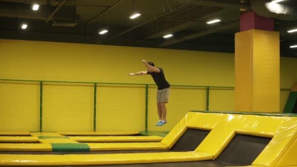 Fiatal, vonzó sportos sportoló végez bukfencet front és a test twistsat profi trambulin képzés.