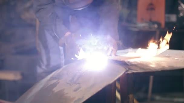 Mužské pracovní ochranné rukavice a oděvy se odřezávají kovodílu oxy acetylenové řezací hořák v továrně. Slow motion záběry.