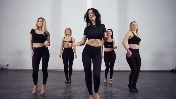 eine Gruppe attraktiver, sportlicher Frauen in schwarzer, aktiver Kleidung tanzt Bachata im Standardkurs