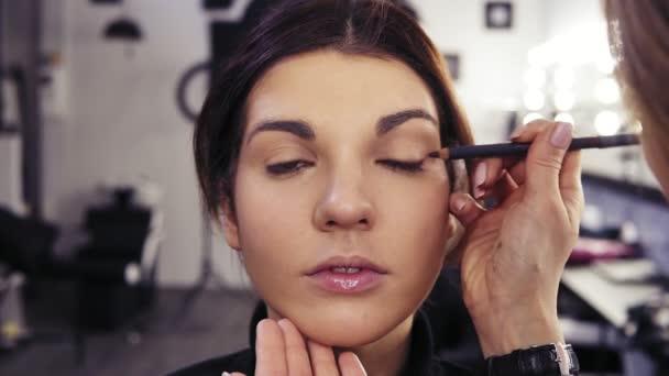 K nepoznání make-upu umělci ruku platí tužka na oči v oči vnější V části krásné atraktivní tmavovláska. Kosmetický salon pozadí.
