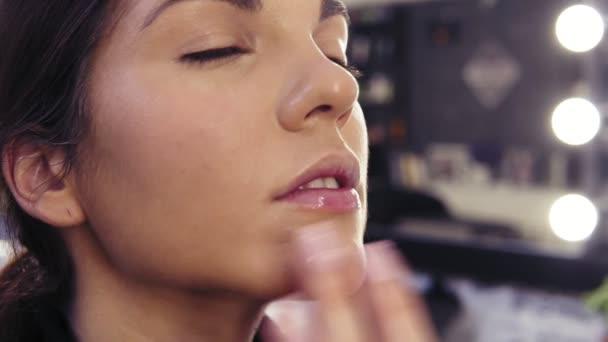 Proces make-upu umělci ruční nanášení korektoru na T-zónu tváře krásné atraktivní dívky v beauty studiu