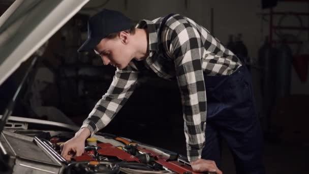 Auto servis, opravy, údržbu a lidé koncept - mechanik muž v práci roucho a SZP pracuje v dílně