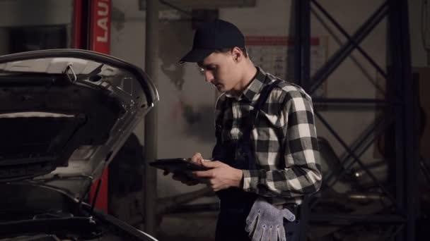 Auto servisní technik pomocí digitálních tabletu zkoumat vnitřek vozidla.