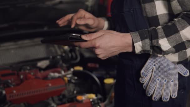 Záběry v pomalém pohybu auto servisní technik pomocí digitálních tabletu otázkami vozidla zblízka. Opravy, údržba, lidé koncept