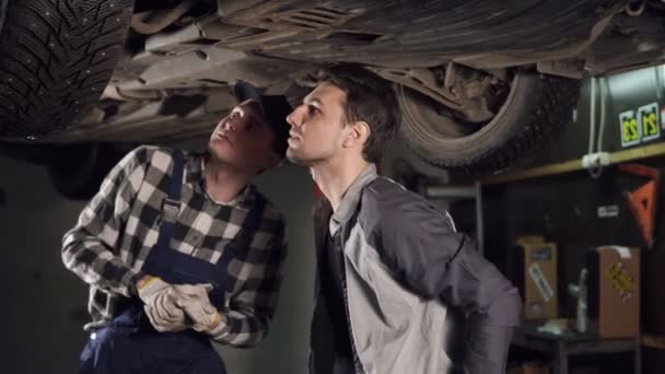 Mechanik a jeho mužské klient kontrolu opraveného veicle. Zákazník třese rukou s auto opravy služby reprezentující.