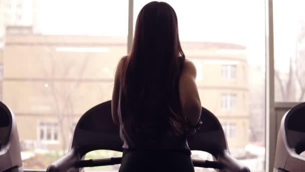 Backside footage of a sportive female athlete with long brunette hair running on treadmill. Indoors. Healthy lifestyle, sports and fitness, wellbeing