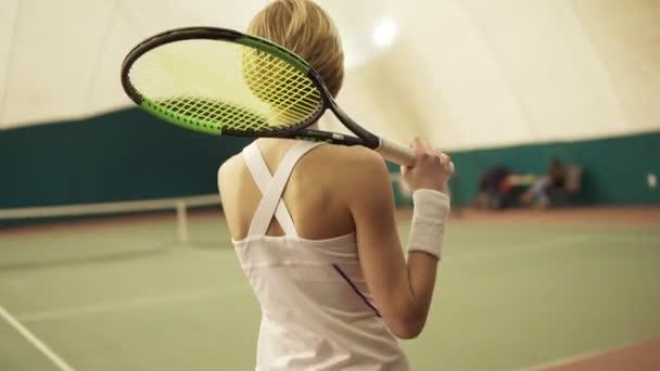 Atraktivní athletewalk s raketou na tenisový kurt chystá hrát