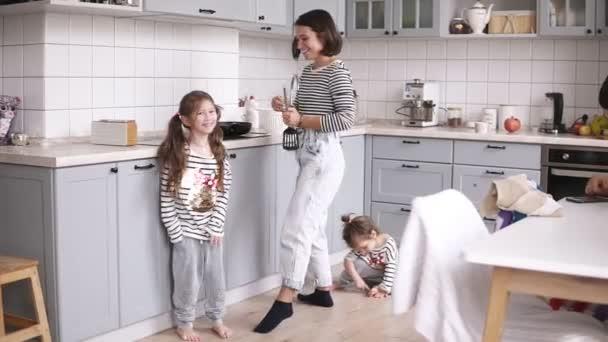 Matka se hraje na stěrky jako je kytara, dvě dcery se tančí v okolí