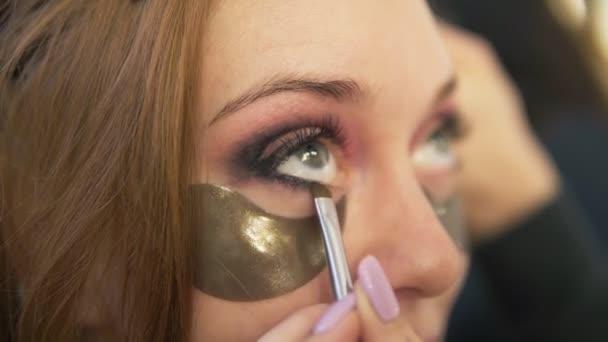 Make-upu kadeřnice dělá smokey oči efekt pro model s pod oči pathes zatímco kadeřník prýmky její vlasy. Detailní záběr
