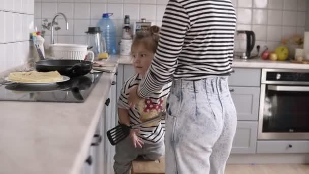 Mladé stylové matka pomáhá dcera obrátit palačinku s lopatou a baví zároveň společné vaření v kuchyni, v domácnosti se dvěma dětmi
