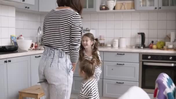 Legrační, mladá a veselá matka hraje s dcerami. Napodobovat koni pomocí lopaty v kuchyni při vaření