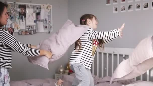 Funny family having a pillow fight in bed. Mother kicks her daughter with pillow and she falling down. Making fun. Slow motion