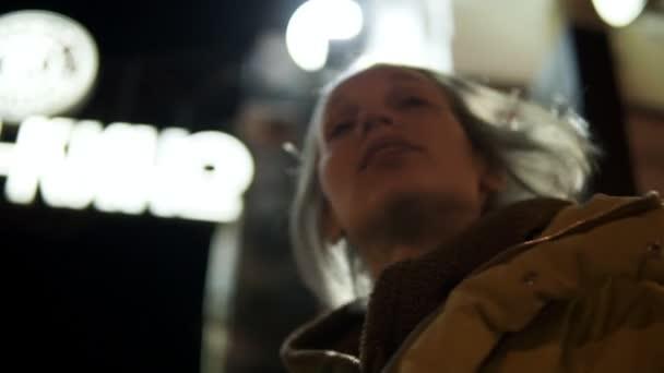 44b475e3434 Souriant de jolie fille lève les yeux à l enseigne lumineuse