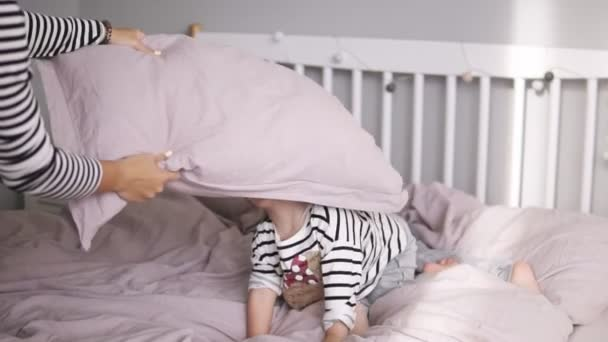 Happy cute daughter with sister and mother have pillows fight lying on a pink bed and have fun in cozy light bedroom. Slow motion