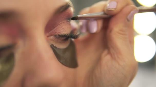 Použití očních stínů na modely očí vizážistka. Zblízka pohled. Opravy