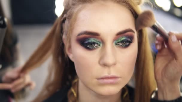 Contouring young models face with big brush and powder. Smoky eyes. Hair stylist behind
