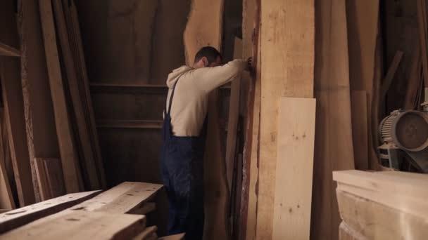 Dělník v truhlářské dílně plné dřeva si vybere vhodného materiálu pro práci. Vysoké kusy dřeva, vybavení a okolí