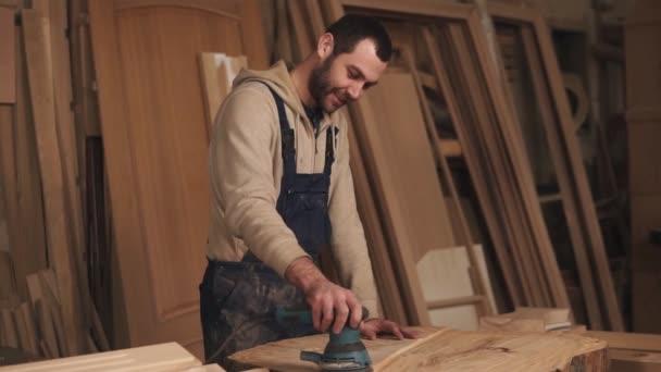 Činnost člověka je leštění kus dřeva s stroj pro broušení v rukou. Dřevěný materiál za