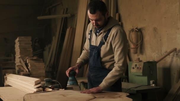Tesařství obchod s dřevěným materiálem, nástroje na pozadí. Truhlářské práce na zpracování dřeva v modré kombinézy. Pečlivě mele materiál s ruční stroj