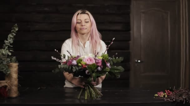 A girl puts on a table a decorated bouquet of flowers. Surprised and laughs. Bouquet in the foreground. The dark interior. Slow motion