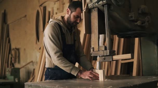 Carpenter shop. A nice worker cuts a ribbed shape from a wooden block using an electric saw machine. Evaluates the work, holding the product in hands