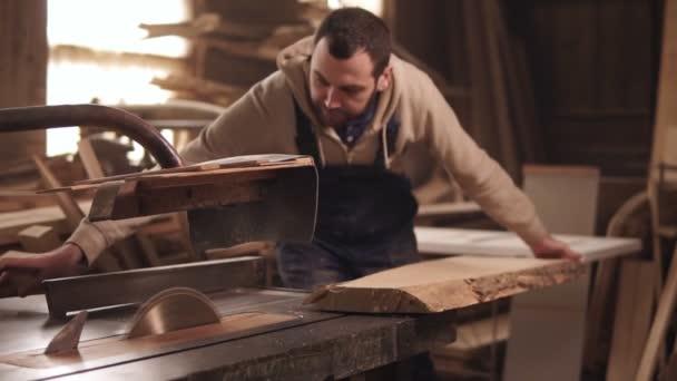 Kotoučová pila v procesu. Carpenter řeže hrany velký kus dřeva. Tesaři dílna