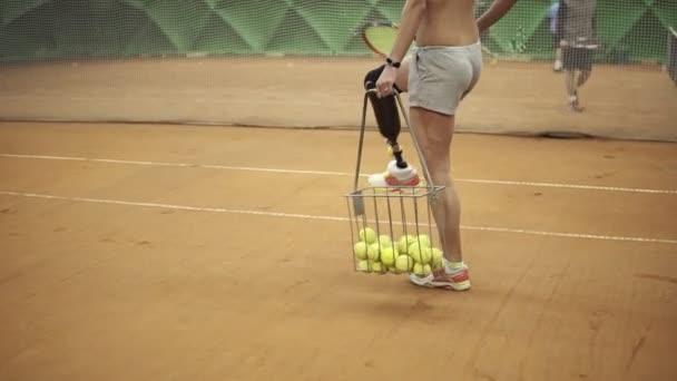 Feche a filmagem de uma jovem com deficiência a apanhar bolas de ténis e  com raquete ... 3b341ddc69819