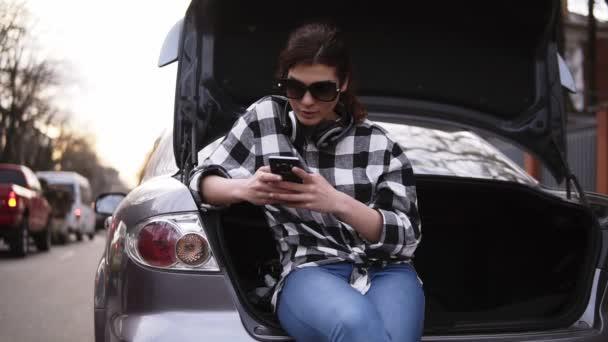 Mulher óculos de sol senta-se no porta-malas aberto do carro em jeans e  camisa xadrez ao longo da rua. Digitando no celular. Fones de ouvido no  pescoço. 04f2874939