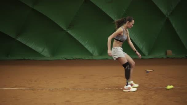 A láb protézisek a sportoló fut körül a bíróság tenisz labdák beállítása a sarkokban. Tréningek. Sportruházat. Beltéri