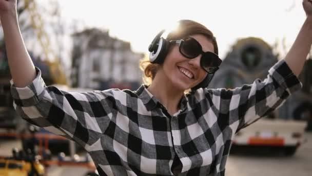Optimistická, šťastné děvče chůzi na ulici a poslouchat dobrou hudbu ve sluchátkách. Ona se směje a tanec. Mává, gestikuloval rukama