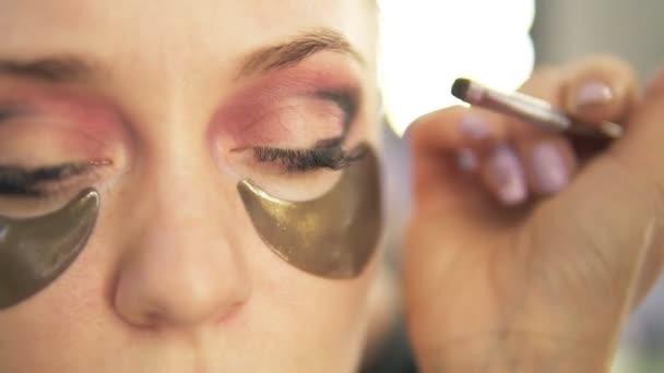 Vizážistka na stíny oční víčka. Světlé vlasy modelu. Zblízka pohled. Kouřové oči, zlaté skvrny pod očima