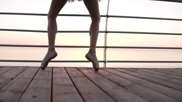 64b1e6e54 Objetivo material de archivo de un pies de bailarines de ballet mientras  ella practica ejercicios de pointe en el terraplén de madera junto a la  mar. Cerca de las piernas de la mujer en los zapatos ...