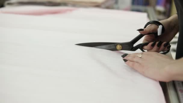 Extrémně detailní záběr záběry ženské prodejce řezání světle barevných tkáně pomocí černé nůžky. Tkanina je na stole