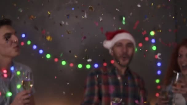 Group of friends celebrating enjoying new years eve party having fun celebration. Friendly and joy. Happy emotion. Christmas decorations at home. Man exploding confetti stick, clinking glasses with