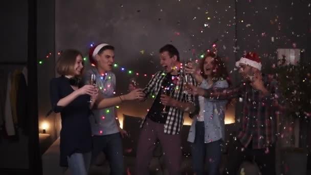 Barevná oslava Vánoc a Nového roku. Slavnostní večírek, skupina pěti cinkajících sklenic se šampaňským poté, co jeden chlap odpálí tyčinku. Šťastná oslava spolu s blízkými přáteli na