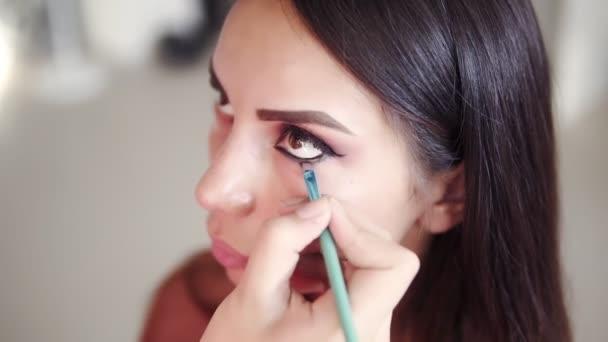 Vysokoúhlé záběry nepoznatelného maskéra, který aplikuje a kombinuje modely s dolním víčkem se stříbrnými stíny očí. Proces vytváření dokonalých kouřových očí tvoří vzhled