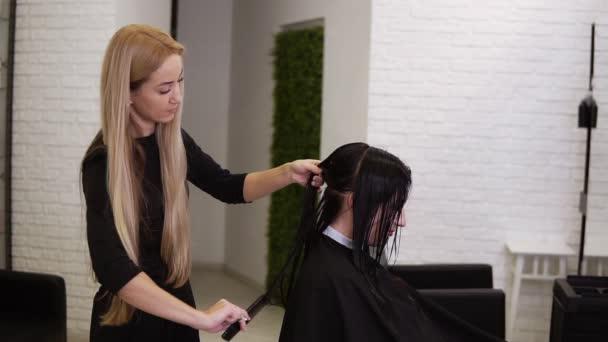 Szőke fodrász ollóval, fésülködéssel és részvény szakaszok ügyfelek nedves haj a tökéletes hajvágás. Fiatal, gyönyörű nő haját vágja a szépségszalonban. A hajvágás folyamata használati ollóval